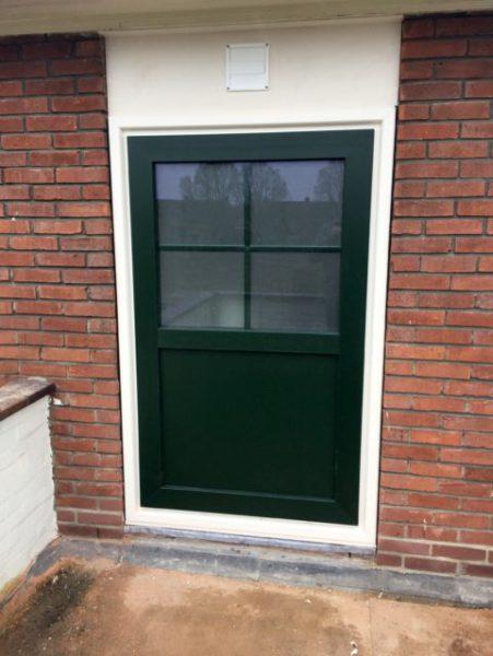 Deze onderhoudsvrije achterdeur met daarboven een ventilatierooster.